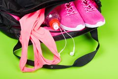 Ropa de deportes y accesorios rosados para la aptitud, en un bolso en un fondo verde claro fotografía de archivo libre de regalías