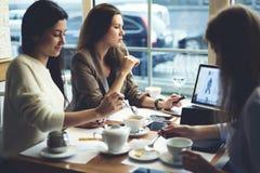 Ropa de diseñadores de las muchachas que trabaja junto fijando el contenido en Internet usando el ordenador portátil con mofa enc Fotografía de archivo