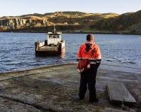 Ropa de funcionamiento que lleva masculina que se coloca en el embarcadero con un lanzamiento del barco foto de archivo