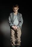 Ropa de gran tamaño que lleva del muchacho enojado en sitio oscuro Fotos de archivo libres de regalías