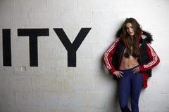 Ropa de la aptitud de la mujer que lleva que se opone a la pared del gimnasio Imagen de archivo