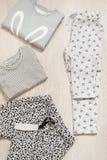 Ropa de la moda de los niños fijada para la muchacha Blusa, pantalones y camisetas en un fondo de madera gris Imagen de archivo