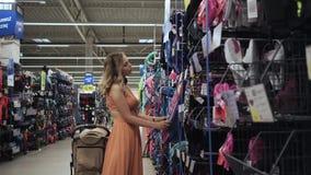 Ropa de la mujer joven en traje de baño en una tienda en el departamento de los deportes metrajes