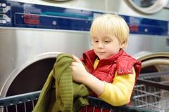 Ropa de las cargas del niño pequeño en la secadora en lavandería automática pública fotografía de archivo
