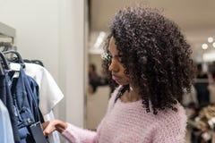 Ropa de las compras de la mujer negra en una tienda Foto de archivo libre de regalías