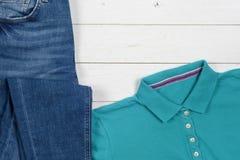 Ropa de las mujeres fijada y accesorios en un fondo de madera rústico Deportes camiseta y zapatillas de deporte en colores brilla Fotografía de archivo