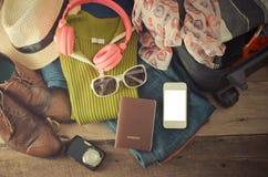 Ropa de los accesorios de vestir del viaje adelante en piso de madera Foto de archivo