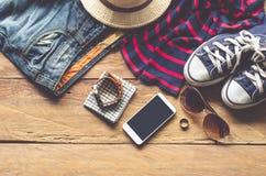 Ropa de los accesorios de vestir del viaje adelante en piso de madera Fotos de archivo