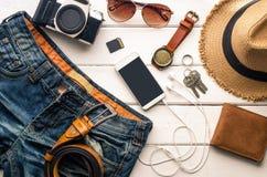 Ropa de los accesorios de vestir del viaje adelante para el viaje en el piso de madera blanco Foto de archivo libre de regalías