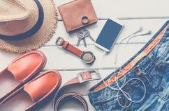 Ropa de los accesorios de vestir del viaje adelante para el viaje en el piso de madera blanco Imagen de archivo