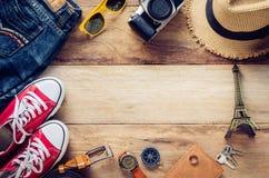 Ropa de los accesorios de vestir del viaje en piso de madera Imagen de archivo