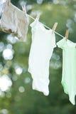 Ropa de los niños que se seca en una cuerda para tender la ropa Fotografía de archivo libre de regalías