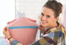 Ropa de medición de la costurera feliz en maniquí Fotografía de archivo libre de regalías