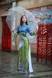Ropa de mujer vietnamita Ao dai que sostiene el paraguas en la lluvia Fotografía de archivo libre de regalías