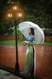 Ropa de mujer vietnamita Ao dai que sostiene el paraguas en la lluvia Foto de archivo