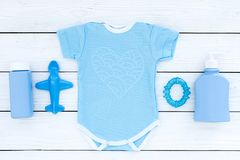 Ropa del bebé azul para el niño pequeño Mono, juguetes, cosméticos en la opinión superior del fondo de madera blanco Imágenes de archivo libres de regalías