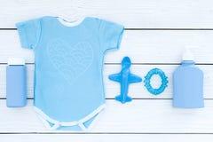 Ropa del bebé azul para el niño pequeño Mono, juguetes, cosméticos en la opinión superior del fondo de madera blanco Foto de archivo