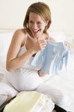 Ropa del bebé del embalaje de la mujer embarazada en maleta Imagen de archivo libre de regalías