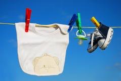 Ropa del bebé en cuerda para tender la ropa Imagen de archivo libre de regalías