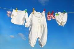 Ropa del bebé en cuerda para tender la ropa Fotografía de archivo libre de regalías