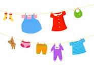 Ropa del bebé en una cuerda para tender la ropa Fotografía de archivo