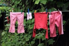 Ropa del bebé que cuelga la línea de ropa Imágenes de archivo libres de regalías