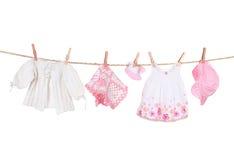 Ropa del bebé que cuelga en una cuerda para tender la ropa Imagen de archivo libre de regalías