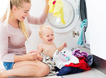 Ropa del cargamento de la madre y del bebé en la lavadora Imagenes de archivo