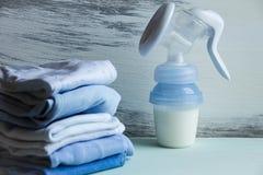 Ropa del cuidado del bebé y bomba de lactancia manual imagen de archivo