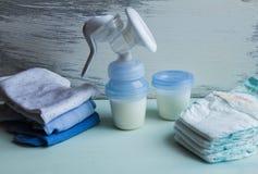Ropa del cuidado del bebé y bomba de lactancia manual imagenes de archivo