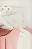 Ropa del ` s de las mujeres en tonos rosados en una suspensión blanca Foto de archivo