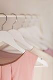 Ropa del ` s de las mujeres en tonos rosados en una suspensión blanca Imagen de archivo libre de regalías