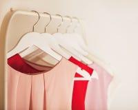 Ropa del ` s de las mujeres en tonos rosados en una suspensión blanca Fotografía de archivo libre de regalías