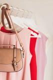 Ropa del ` s de las mujeres en tonos rosados en una suspensión blanca Imagenes de archivo