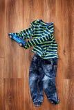 Ropa del ` s de los niños de la primavera o del verano y coche azul del juguete en el fondo de madera Imagen de archivo libre de regalías
