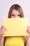 Ropa del yelow de la muchacha que desgasta y mostrar la tarjeta en blanco Imagen de archivo libre de regalías