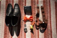 Ropa determinada del novio Anillos de bodas, zapatos, mancuernas y corbata de lazo Imágenes de archivo libres de regalías