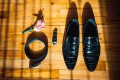Ropa determinada del novio Anillos de bodas, zapatos, mancuernas y corbata de lazo Imagen de archivo