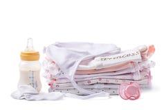 Ropa doblada para los bebés con una botella de leche y de pacificador Fotos de archivo
