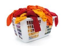Ropa en cesta de lavadero. Rojo, anaranjado, amarillo. Foto de archivo libre de regalías