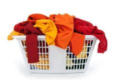 Ropa en cesta de lavadero. Rojo, anaranjado, amarillo. Foto de archivo