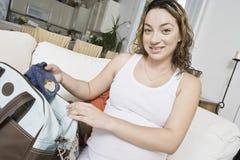 Ropa expectante del bebé del embalaje de la mujer imágenes de archivo libres de regalías