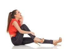 Ropa flickasammanträde på golvet Arkivfoton