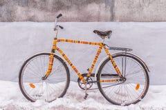 Ropa hecha punto aislada bici adornada en una calle nevosa Foto de archivo