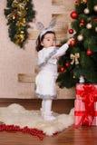Ropa informal que lleva de la pequeña muchacha linda asiática que presenta cerca de árbol clásico del verde de la Navidad del Año Fotografía de archivo