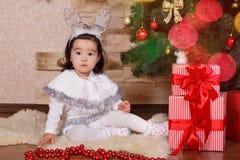 Ropa informal que lleva de la pequeña muchacha linda asiática que presenta cerca de árbol clásico del verde de la Navidad del Año Fotos de archivo