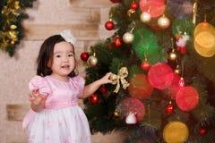 Ropa informal que lleva de la pequeña muchacha linda asiática que presenta cerca de árbol clásico del verde de la Navidad del Año Imagenes de archivo