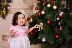 Ropa informal que lleva de la pequeña muchacha linda asiática que presenta cerca de árbol clásico del verde de la Navidad del Año Fotos de archivo libres de regalías