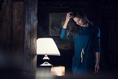 Ropa informal que lleva del retrato de la mujer que sonríe y que lo mira abajo de la lámpara cercana sala de estar interior caser fotografía de archivo