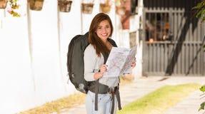 Ropa informal que lleva y mochila de la mujer bonita joven que se colocan delante de la cámara, sonriendo feliz, sosteniendo el m Fotografía de archivo libre de regalías